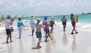 people doing tai chi on the beach