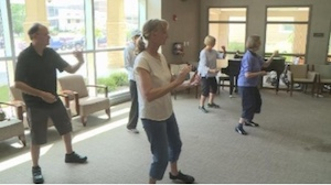 adults doing tai chi in classroom